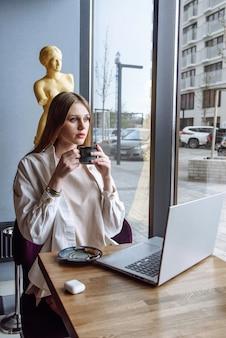 Młoda kobieta interesu pije kawę w restauracji i pracuje na laptopie