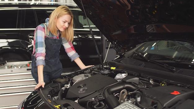 Młoda kobieta interesuje się naprawą samochodu, ulubionym hobby