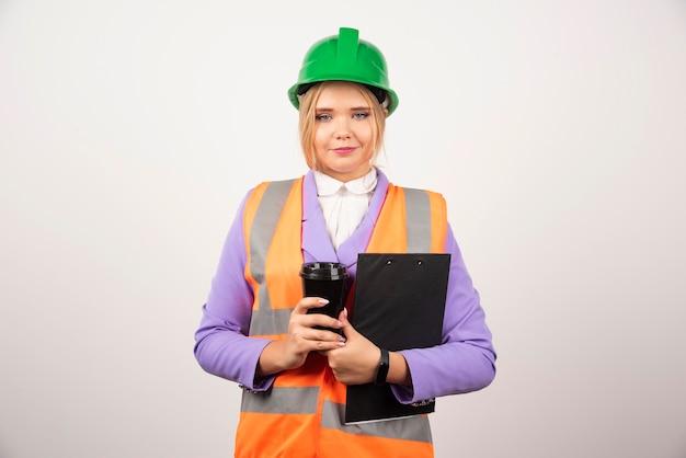 Młoda kobieta inżynier przemysłowy w mundurze ze schowka i czarny kubek na białym tle.
