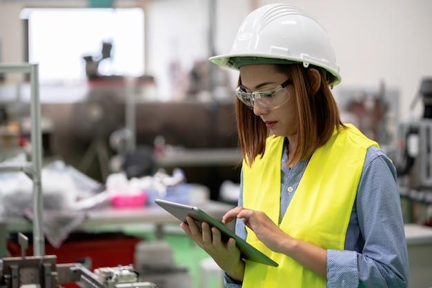 Młoda kobieta inżynier sprawdza programowanie w fabryce automatyki.