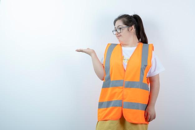 Młoda kobieta inżynier w okularach, trzymając otwartą przestrzeń na białej ścianie