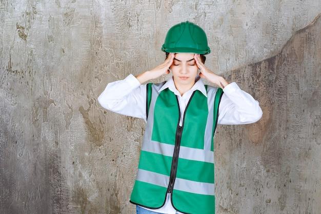 Młoda kobieta inżynier w zielonej kamizelce i kasku trzymająca głowę