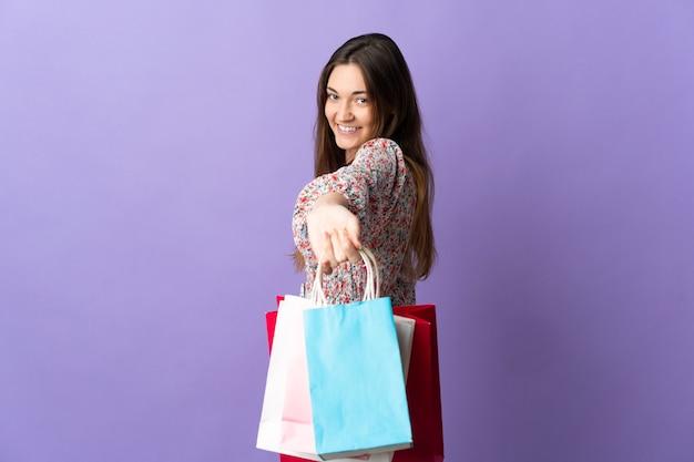 Młoda kobieta irlandii na białym tle na fioletowym tle, trzymając torby na zakupy i dając je komuś