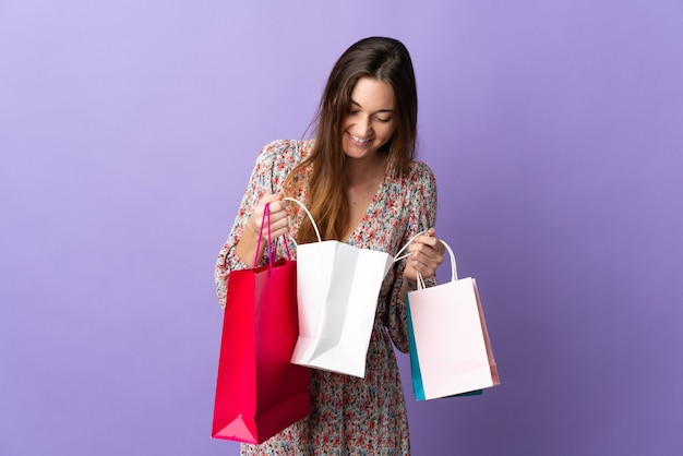 Młoda kobieta irlandii na białym tle na fioletowym tle, trzymając torby na zakupy i patrząc wewnątrz niego