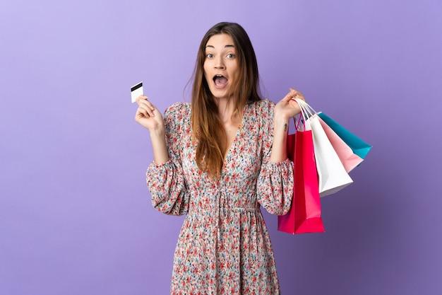 Młoda kobieta irlandii na białym tle na fioletowym tle trzymając torby na zakupy i zaskoczony