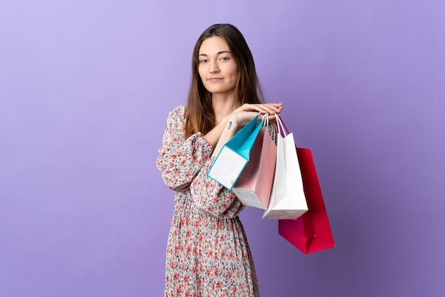 Młoda kobieta irlandii na białym tle na fioletowym tle trzymając torby na zakupy