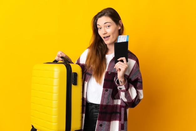 Młoda kobieta irlandii na białym tle na żółtym tle w wakacje z walizką i paszportem