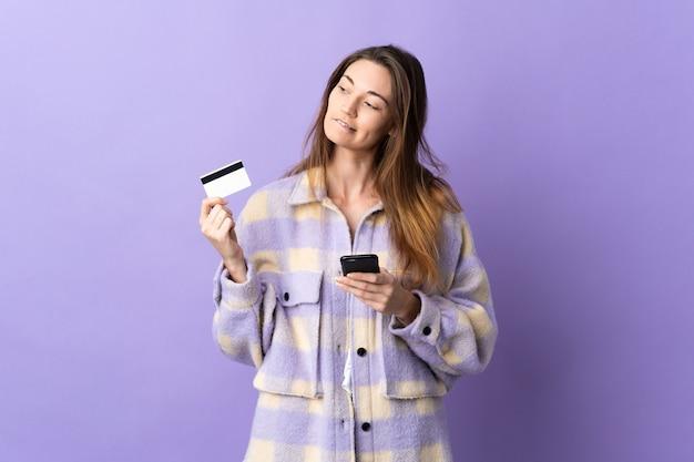 Młoda kobieta irlandii samodzielnie na fioletowej ścianie kupując telefon komórkowy za pomocą karty kredytowej podczas myślenia