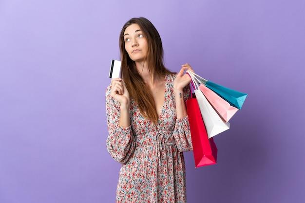 Młoda kobieta irlandii samodzielnie na fioletowym tle trzymając torby na zakupy i kartę kredytową
