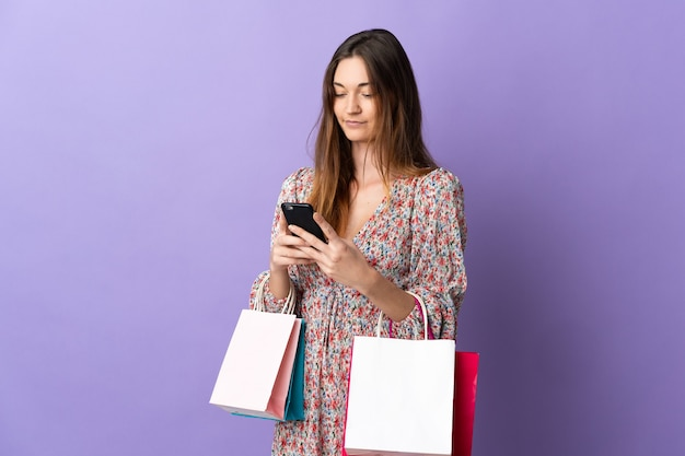 Młoda kobieta irlandii samodzielnie na fioletowym tle, trzymając torby na zakupy i pisząc wiadomość z jej telefonu komórkowego do znajomego