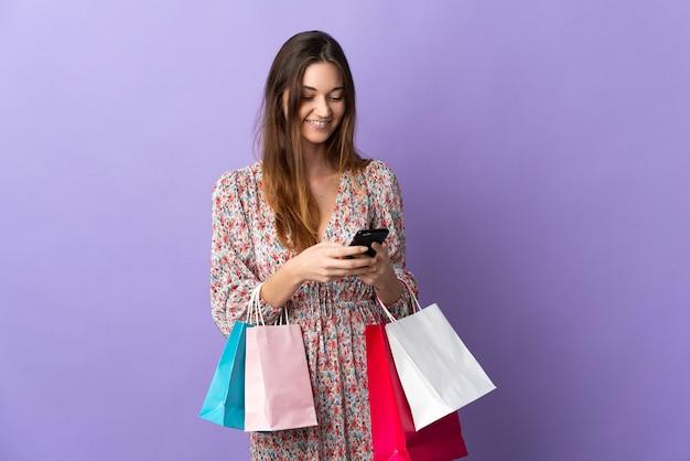Młoda kobieta irlandii samodzielnie na fioletowym tle, trzymając torby na zakupy i pisząc wiadomość ze swoim telefonem komórkowym do znajomego