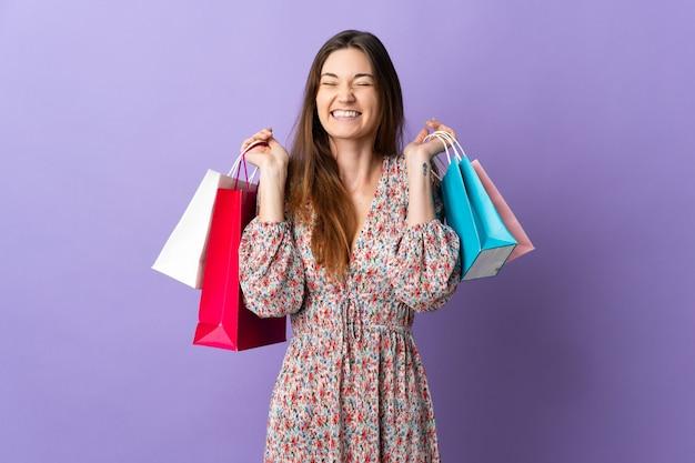 Młoda kobieta irlandii samodzielnie na fioletowym tle trzymając torby na zakupy i uśmiechnięte