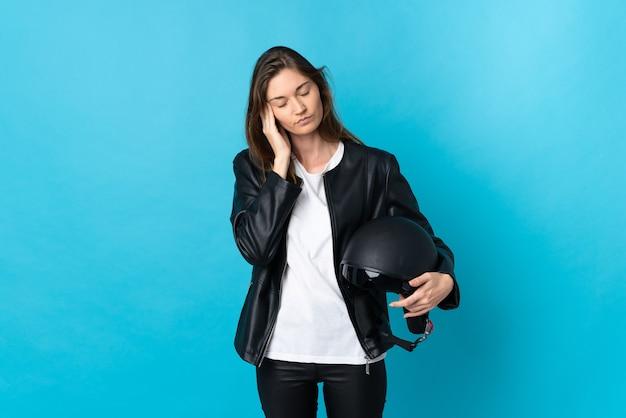 Młoda kobieta irlandii trzymając kask motocyklowy na białym tle na niebieskiej ścianie z bólem głowy