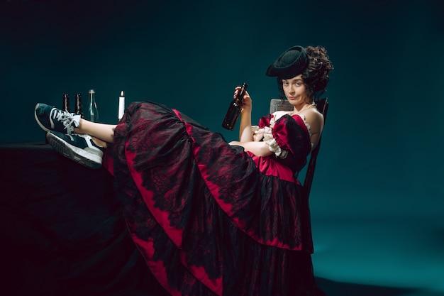 Młoda kobieta jako anna karenina na ciemnym niebieskim tle. styl retro, porównanie koncepcji epok.