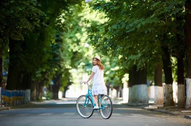 Młoda kobieta jazda rowerem miejskim niebieski odkryty