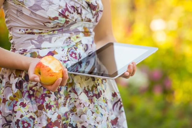 Młoda kobieta je jabłka i bawić się na pastylka komputerze osobistym w parku