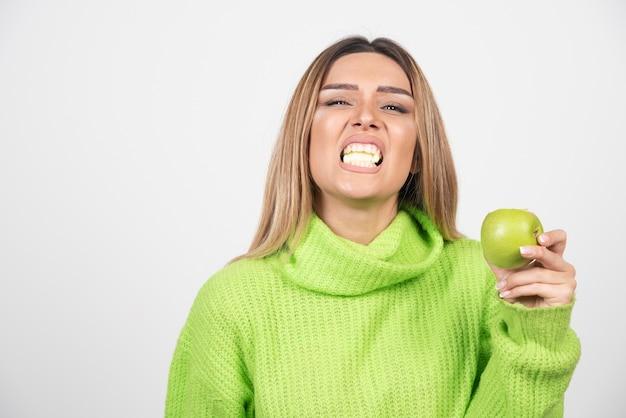 Młoda kobieta je jabłka w zielonej koszulce