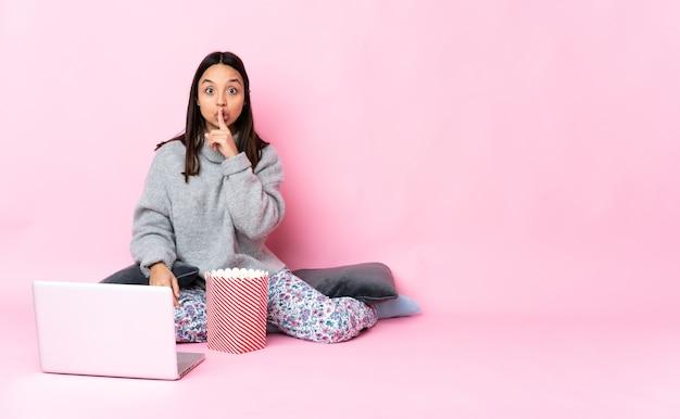 Młoda kobieta je popcorn podczas oglądania filmu na laptopie pokazując znak gestu ciszy wkładając palec do ust