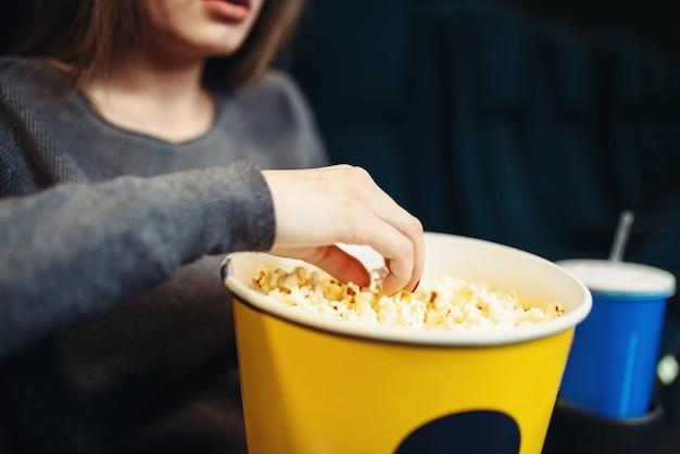 Młoda kobieta je popcorn podczas oglądania filmu w kinie. czas na przedstawienie