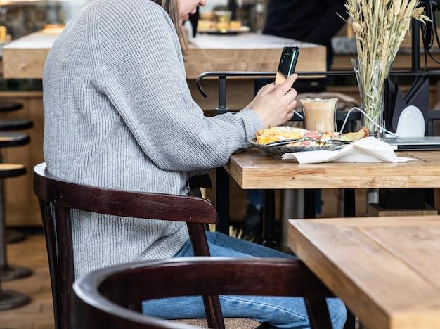 Młoda kobieta je pyszne śniadanie z omletem, rogalikiem i kawą w kawiarni i używając smartfona