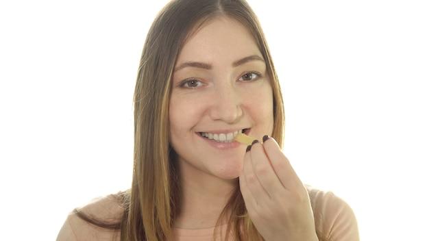 Młoda kobieta je smażone ziemniaki, szkodliwe jedzenie.