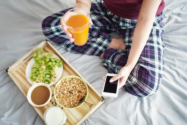 Młoda kobieta je śniadanie w łóżku