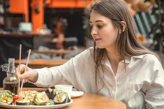 Młoda kobieta je świeżego suszi i cieszy się