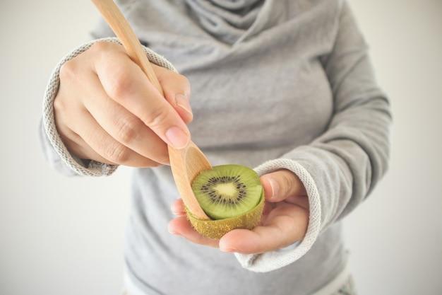Młoda kobieta jedzenie dojrzałe kiwi z drewnianą łyżką