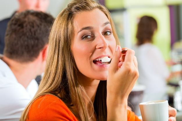 Młoda kobieta jedzenie krem w kawiarni