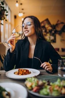 Młoda kobieta jedzenie makaronu w kawiarni