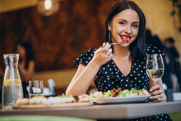 Młoda kobieta jedzenie sałatki w kawiarni