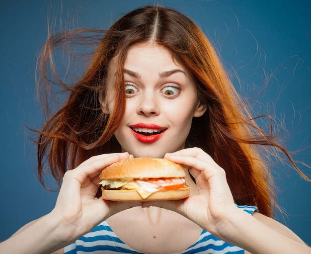 Młoda kobieta, jedzenie soczystego burgera, pyszny hamburger fast food w studio