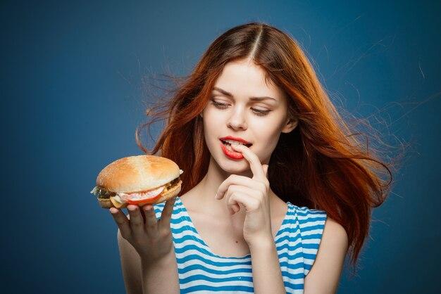 Młoda kobieta jedzenie soczystego hamburgera, pyszne hamburgery fast food