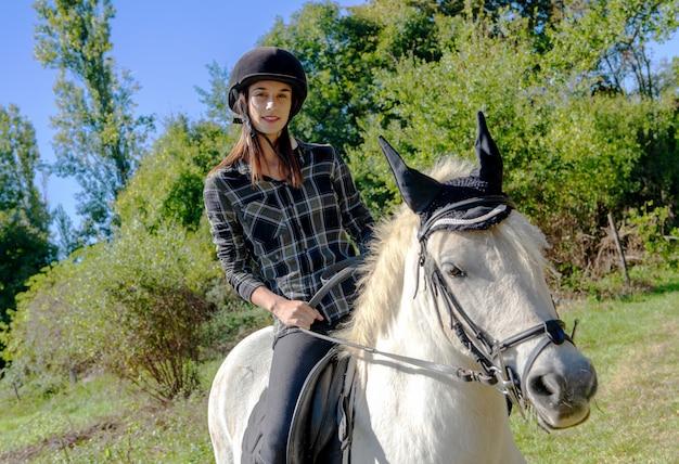 Młoda kobieta jedzie białego konia z czarnym hełmem