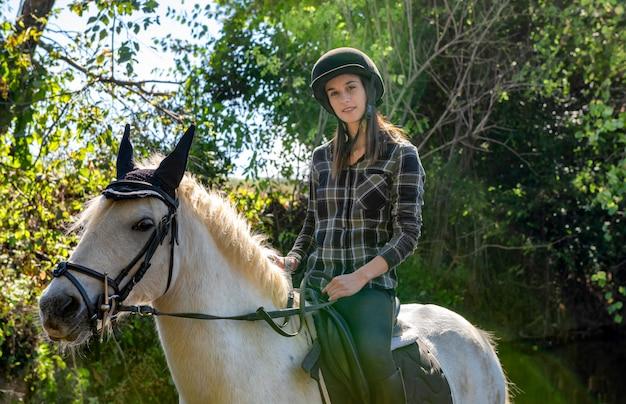 Młoda kobieta jedzie białego konia