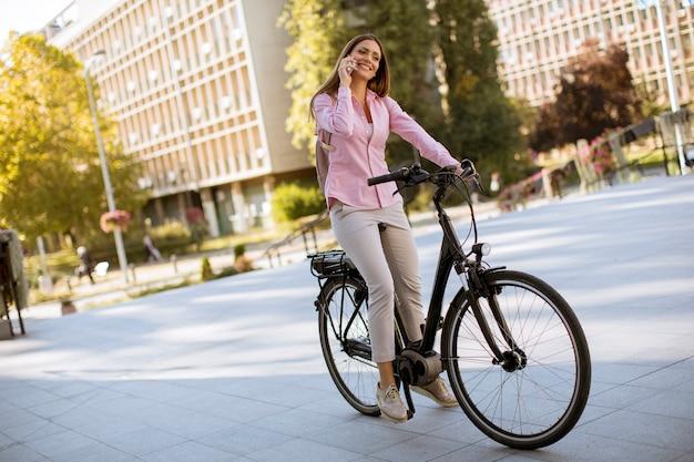 Młoda kobieta jedzie elektrycznego bicykl i używa telefon komórkowego