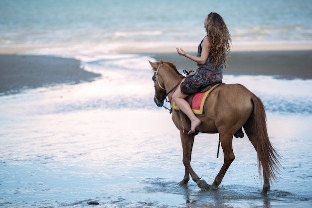 Młoda kobieta jedzie konia przy plażą, wakacje wycieczki pojęcie.
