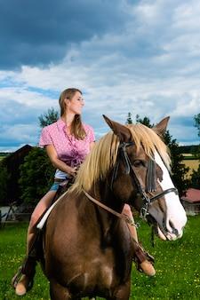 Młoda kobieta jedzie konie na łące