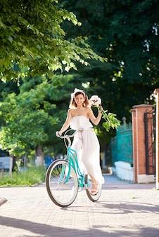 Młoda kobieta jedzie na zewnątrz niebieski rower miejski