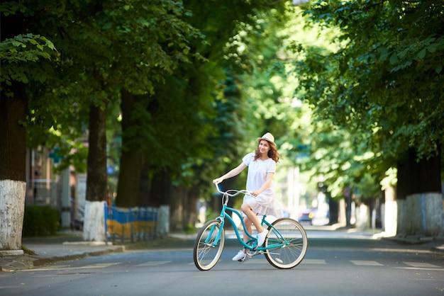 Młoda kobieta jedzie niebieski rower na zewnątrz