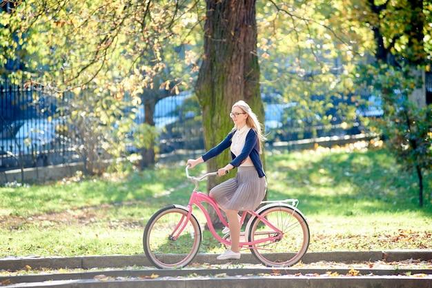 Młoda kobieta jedzie rowerem pani różowy wzdłuż brukowanego chodnika w parku w jasny słoneczny jesienny dzień