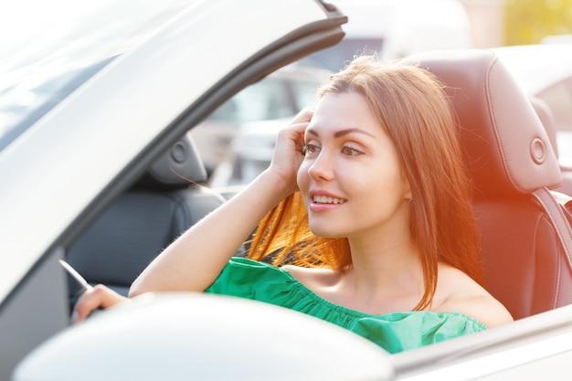 Młoda kobieta jedzie samochód w mieście.