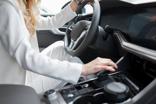 Młoda kobieta jedzie samochód.