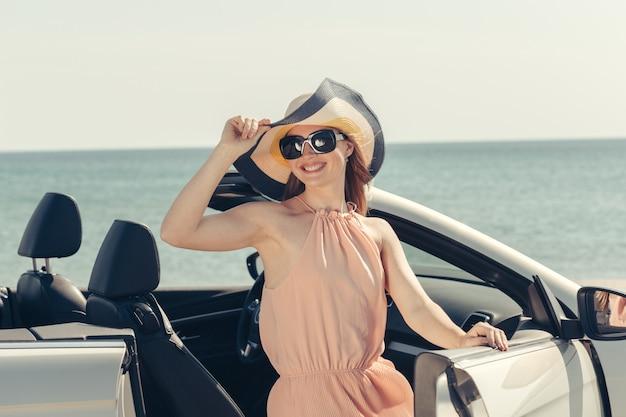Młoda kobieta jedzie samochodem na plaży