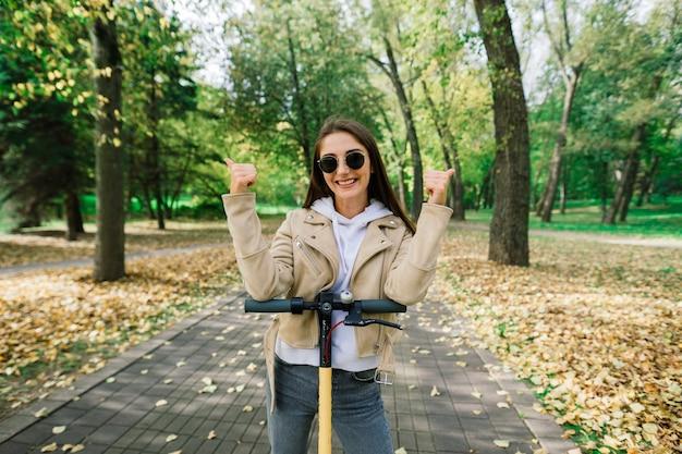 Młoda kobieta jedzie skuterem elektrycznym w jesiennym parku. zielony transport, problemy z korkami.