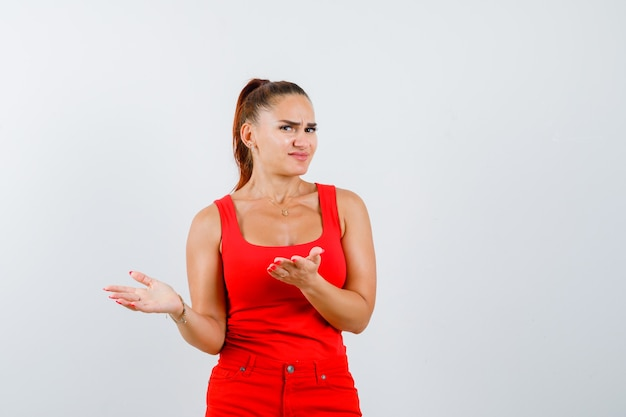 Młoda kobieta jest niezadowolona z głupiego pytania w czerwonej koszulce bez rękawów, spodniach i wygląda na zdziwioną, widok z przodu.
