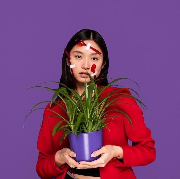 Młoda kobieta jest pokryta plastikowymi łyżkami i widelcami, trzymając roślinę