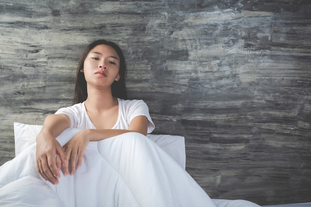 Młoda kobieta jest przygnębiona na białym łóżku