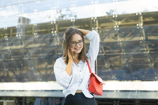 Młoda kobieta jest ubrana w stylu biznesowym, rozmawia przez telefon