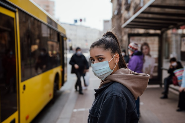 Młoda kobieta jest ubranym chirurgicznie maskę plenerową przy autobusową przerwą na ulicie